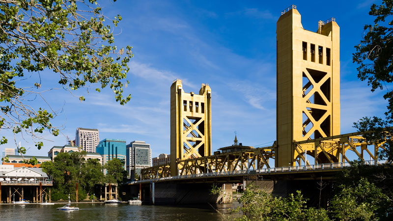 Yellow bridge over water and downtown Sacramento buildings providing remote collection services